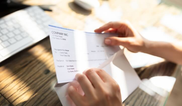 Opening envelope containing paycheck