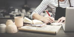 Arm of a woman sitting at a desk with sleeve pushed up, pencil in hand, notebook open and plans laid out on the desk